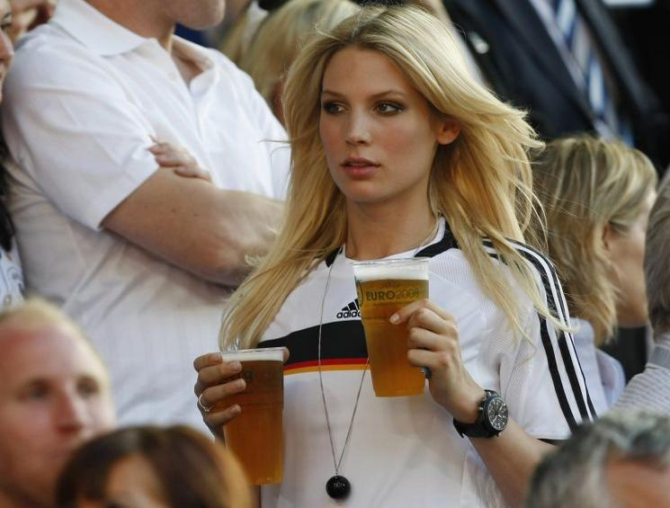 Sarah Brandner, the partner of Germany's national soccer player Bastian Schweinsteiger, carries beers before their Euro 2008 quarter-final match against Portugal at St Jakob Park stadium in Basel, June 19, 2008.     REUTERS/Alex Grimm (SWITZERLAND)   MOBILE OUT. EDITORIAL USE ONLY